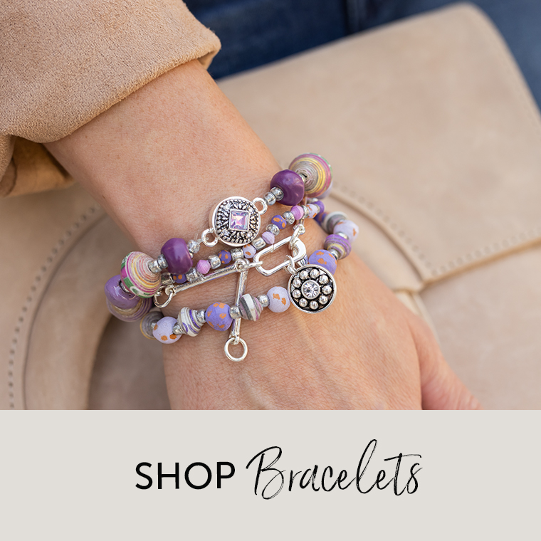 Woman wearing bracelets with dots and beads in varying shades of purple