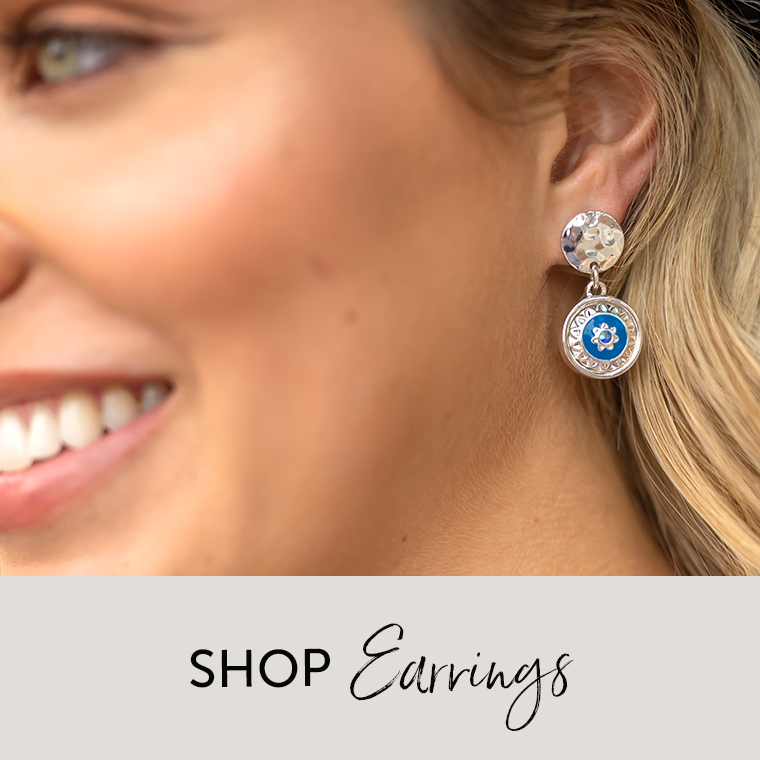 Woman with earrings featuring a blue and silver dot