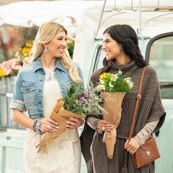 Two well-dressed women at a flower market